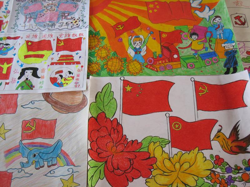"""老师在同学们画""""三旗""""的过程中给他们讲述国旗,党旗,团旗的来历和含意"""
