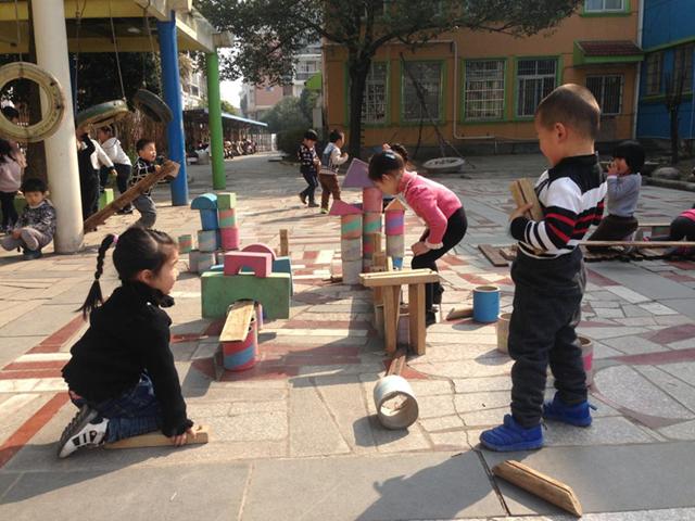 最近是安吉机关幼儿园小四班的小朋友玩户外建构游戏。我们的孩子在建构中不断地发展他们的各项技能。在整个过程中,我看到了孩子的建构技能从原来的平铺到垒高、空间以及组合等认知发展;我聆听到孩子们从无意识的搭建到初步的有计划地搭建;我看到更多的孩子从以前的单独游戏走向交流、合作、探索的游戏过程;最后,我也发现孩子们拥有一颗永远好奇的心灵和无穷尽的想象力。