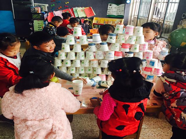 纸杯是我们常见的生活用品,它是很好的垒高材料。垒高游戏是对孩子手眼协调能力的高度挑战。在垒高中,孩子们必须聚精会神,在操作中一次次勇敢地去挑战高度的极限。近日,天荒坪幼儿园大一班在积木区投放了一筐的纸杯,游戏中纸杯一直深受孩子们的欢迎,在游戏过程中,孩子们通过语言的交流进行合作,不断丰富着主题内容,运用了平铺、延长、接插、垒高、对称、围合盖顶等方法,体验到自己与同伴共同搭建的快乐感、成功感。孩子们在玩的过程中提高了建构技能,培养孩子的创造、合作能力。