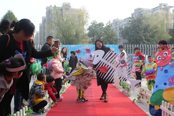 孩子和家长穿上了用废旧材料精心制作的动物服装,有的穿着用纸箱和